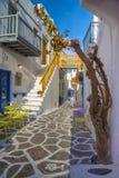 Streetview de la ciudad de Mykonos con las sillas y tablas y escaleras amarillas, Grecia Imagenes de archivo