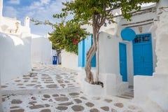 Streetview de Mykonos con la puerta y los árboles azules, Grecia Fotografía de archivo libre de regalías