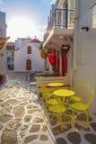 Streetview de Mykonos en la salida del sol con la capilla y sillas y tablas amarillas, Grecia Fotografía de archivo libre de regalías