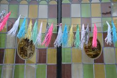 Partytime, garlands before a window. Streetview with garlands hanging in front of glass and lead window Royalty Free Stock Images