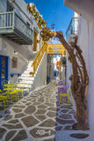Streetview of Mykonos town with yellow chairs and tables and stairs, Greece Stock Images