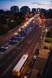 Streetview na noite com um ônibus na estrada e em carros de estacionamento fotografia de stock royalty free