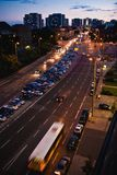 Streetview by night with a bus on road and parking cars royalty free stock photography