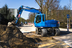 Streetwork with draglines. Draglines at work to renew the pavement of a road in the city. Blue excavators and bright blue sky in early spring. Horizontal image Stock Image