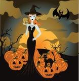 Strega di Halloween che si leva in piedi con il cranio e la zucca Fotografie Stock Libere da Diritti