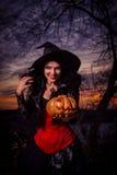 Strega di Halloween che tiene una zucca Fotografia Stock Libera da Diritti