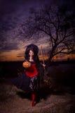 Strega di Halloween con una zucca e una scopa Fotografie Stock