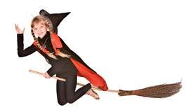 Strega di Halloween della ragazza del bambino in mosca nera sulla scopa. Immagini Stock Libere da Diritti