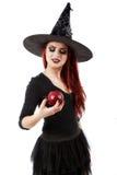 Strega ingannevole che offre una mela avvelenata, tema di Halloween Immagine Stock