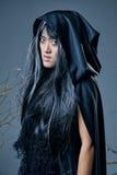 Strega in mantello nero Immagine Stock