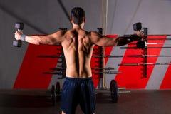Streghi la retrovisione di allenamento dell'uomo delle teste di legno alla palestra Immagine Stock