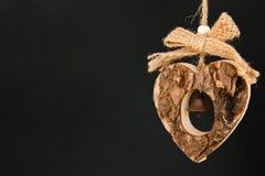 Streifen Sie hölzernes Herz auf einem Seil mit weniger undurchsichtiger Messingglocke in ab lizenzfreie stockfotos