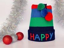 Streifen stricken Hut mit den mehrfarbigen das GLÜCKLICHE und drei Wort Pompoms, roten und silbernen den Weihnachtsbällen und dem lizenzfreie stockbilder