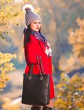 Strelnikova_Svetlana. Woman red coat and gray hat, black leather. Beautiful sensuality elegance brunette woman, has happy fun cheerful smiling face, brown eyes Stock Images