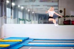 Streng die jonge vrouw op de trampoline springen stock foto