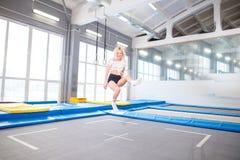 Streng die jonge vrouw op de trampoline springen stock fotografie