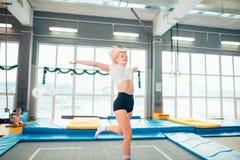 Streng die jonge vrouw op de trampoline springen stock foto's