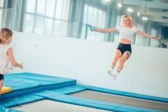 Streng die jonge vrouw op de trampoline springen stock afbeeldingen