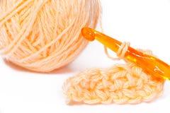 Streng van oranje garen close-up en het haken Stock Afbeeldingen