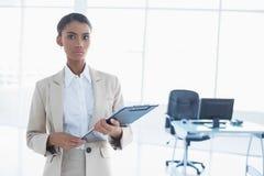 Strenge elegante Geschäftsfrau, die Klemmbrett hält Stockfotografie