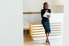 Strenge elegante Geschäftsfrau, die schwarzes Kleid und beige Schuhe im hellen Büro blickt in Richtung mit ihrer Tagesordnung, Ha Stockfoto
