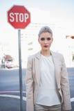 Strenge elegante Geschäftsfrau, die draußen aufwirft Stockfotografie