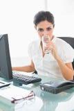 Strenge Geschäftsfrau, die ein Glas Wasser an ihrem Schreibtisch trinkt Lizenzfreie Stockbilder