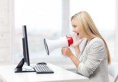 Strenge Geschäftsfrau, die im Megaphon schreit Stockbild