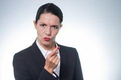 Strenge junge Frau, die eine Fingergeste macht Stockfotografie