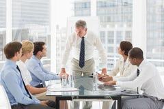 Strenge zakenman die neer zijn personeel tijdens een vergadering bekijken royalty-vrije stock afbeeldingen