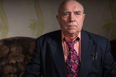 Strenger alter Geschäftsmann, der in seinem Raum sitzt Lizenzfreie Stockbilder