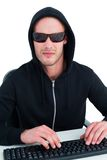 Strenger Hacker mit Sonnenbrille schreibend auf Tastatur Stockfoto