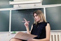 Strenger junger blonder Lehrer denkt über wem nach, um Hausarbeit zu überprüfen Stockfotografie