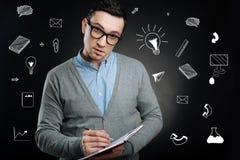Strenger Lehrer, der seinen Kopf bei der Stellung mit einem Notizbuch lehnt Stockbilder