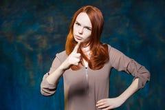 Strenges rotes behaartes Mädchen zeigt Finger mit den in die Seite gestemmten Armen Stockbilder