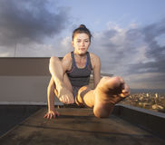 Strenght. Girl making an advanced yoga balance on a rooftop at dawn Stock Photography