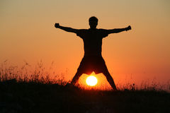 Strenght. A man is playing with the sun Royalty Free Stock Photos