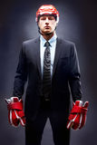 Strength. Portrait of young businessman in suit and hockey helmet and gloves royalty free stock photos