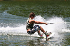 Strength. Teenage boy showing strength and power on the wakeboard stock photo