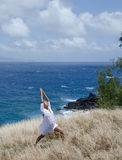 Strength and Calm Yoga. Young woman practices yoga in the sun on a grassy cliff above a turquoise ocean Stock Photo