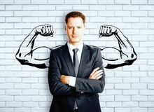 Strength concept. Confident businessman with drawn muscly hands on brick background. Strength concept stock image