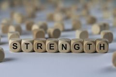 Strength - cube with letters, sign with wooden cubes. Strength - wooden cubes with the inscription `cube with letters, sign with wooden cubes`. This image Stock Image