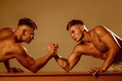 Strength and endurance. Twins men competing till victory. Twins competitors arm wrestling. Men competitors try to win. Victory or revenge. Strength skills stock photo