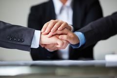 Strength. Image of business partners hands on top of each other symbolizing companionship and unity Stock Images