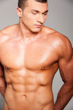 Strength and masculinity. Handsome young muscular man posing while standing against grey background Royalty Free Stock Photo