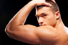 Strength and masculinity. Rear view of handsome young muscular man posing while standing against grey background Royalty Free Stock Images