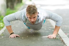 Strength and motivation. Man in sportswear doing push ups outdoor. Guy motivated workout in park. Sportsman improves his. Strength by push up exercise. Man has Stock Image