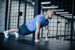 Strength and motivation. Side view of young handsome bald man in sportswear doing push-up at gym royalty free stock image