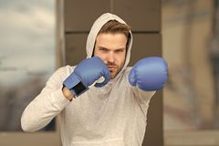 Strength and motivation. Sportsman concentrated training boxing gloves. Athlete concentrated face with sport gloves. Practice fighting skills urban background stock photography