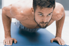 Strength and motivation. Young handsome man doing push-up at gym. Strength and motivation Stock Photo